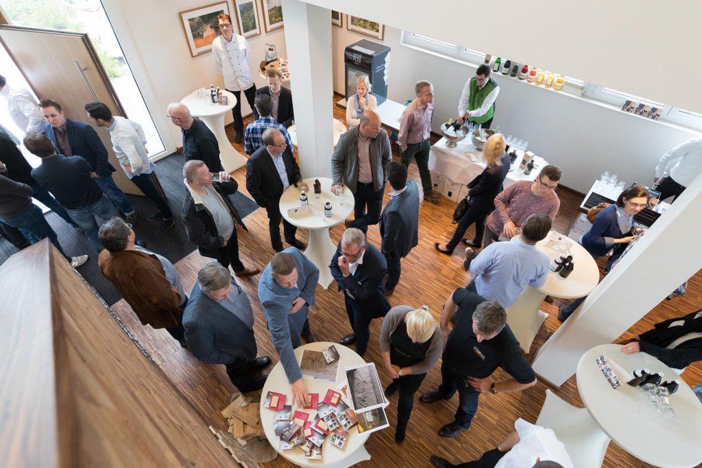 Foyer Coffee Consulate. Viele Personen stehen um Stehtische verteilt und unterhalten sich.